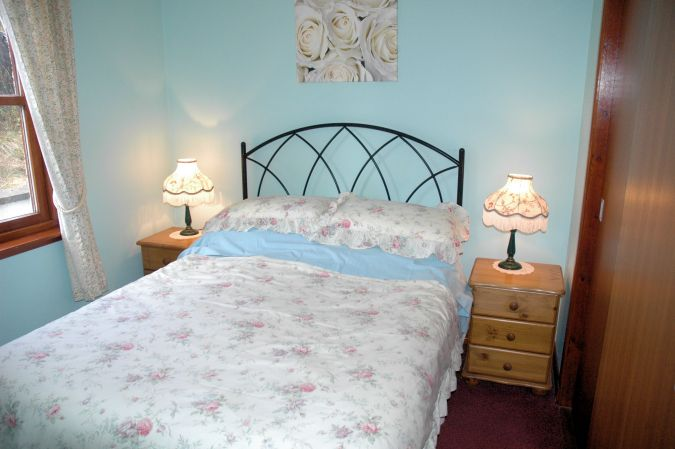 The Double Bedroom is comfortably appointed with bedside tables and lamps, and a built-in wardrobe.