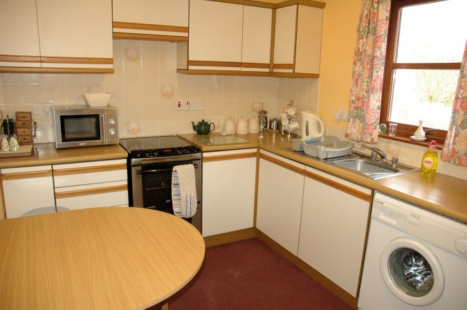 The kitchen in Tarlogie is well equipped with cupboards, work tops and appliances and also has a dining table and chairs.