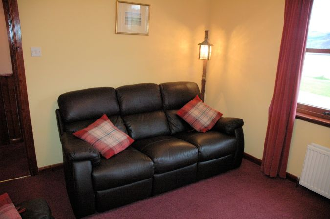 The lounge/sitting room in Tarlogie is comfortably furnished with 2 leather settees.