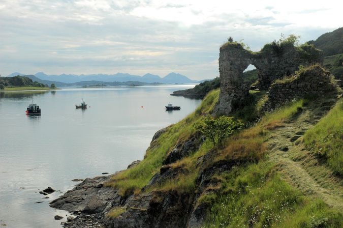 This view shows the Strome Castle ruins standing on their rocky promontory with the Cuillins on Skye in the background.